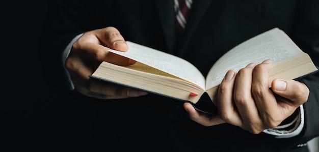 Gros plan homme lisant un livre, montre une main en gros plan et un livre.