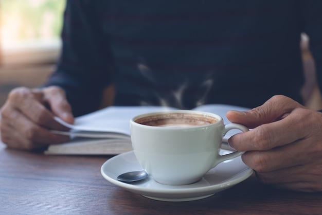 Gros plan d'un homme lisant un livre et une tasse de café sur la table