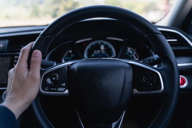 Gros plan de l'homme de main tenant le volant dans la voiture moderne