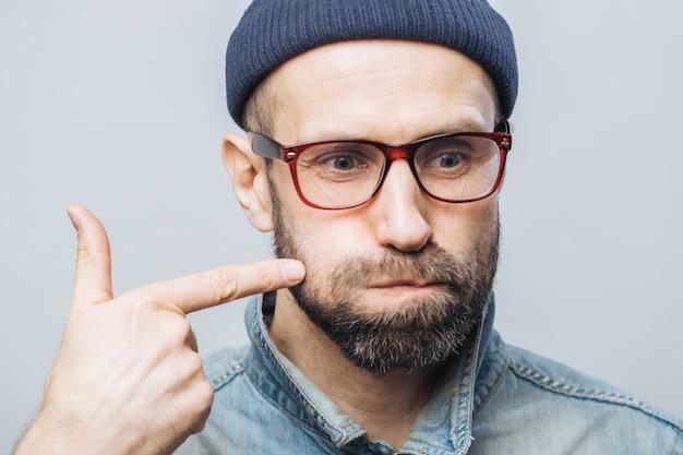 Gros plan d'un homme mal rasé avec une barbe épaisse et une moustache qui souffle sur les joues et indique avec l'index