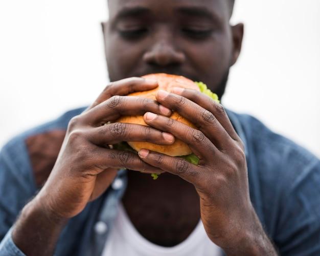 Gros plan, homme, manger, hamburger