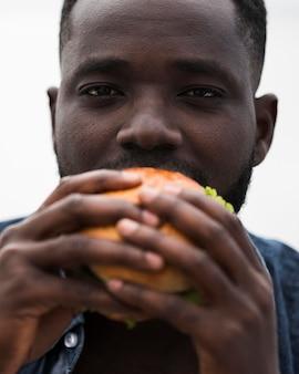 Gros plan, homme, manger, savoureux, hamburger
