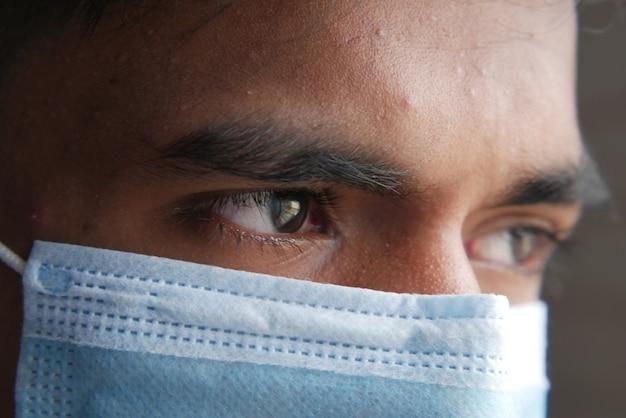 Gros plan d'un homme avec un masque protecteur regardant la caméra
