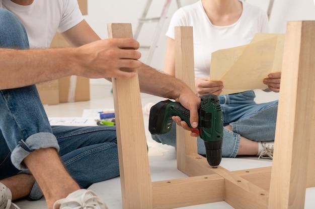 Gros plan d'un homme méconnaissable assis sur le sol et à l'aide d'un tournevis lors de l'assemblage de la table avec sa femme