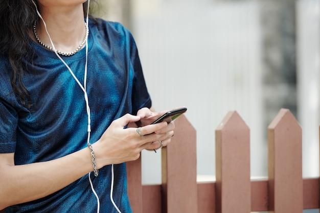 Gros plan d'un homme méconnaissable en t-shirt abstrait bleu écoutant de la musique dans des écouteurs filaires tout en prenant note dans le téléphone