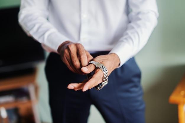 Gros plan d'un homme mettant la montre sur sa main.
