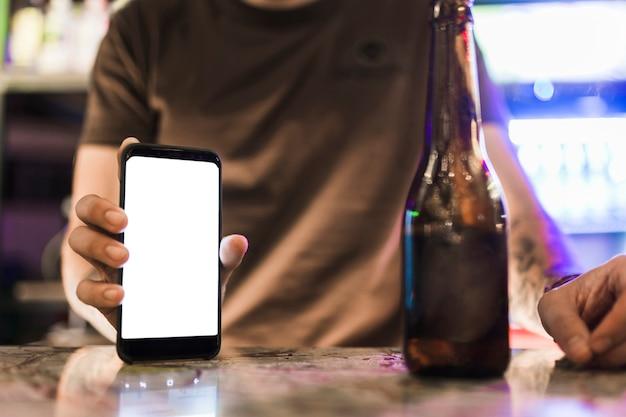 Gros plan de l'homme montrant un écran mobile blanc blanc avec une bouteille de bière sur la table