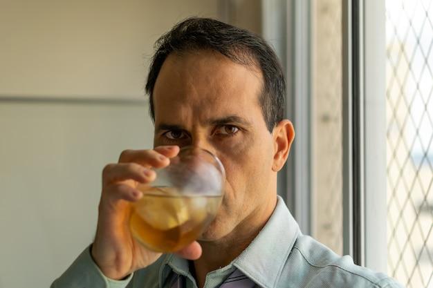 Gros plan d'un homme mûr (44 ans) buvant du whisky à côté d'une fenêtre et regardant la caméra (se concentrer sur l'œil droit).
