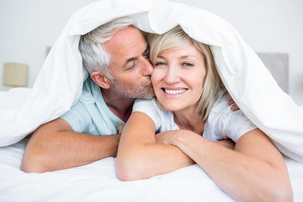 Gros plan d'un homme mûr embrassant la joue de womans dans son lit