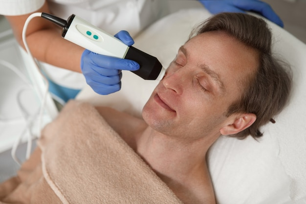Gros plan d'un homme mûr se détendre à la clinique de beauté pendant le traitement cosmétique du matériel