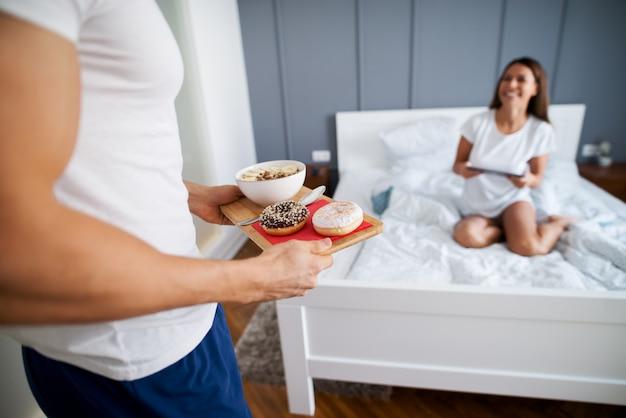 Gros plan d'un homme musclé apportant des beignets et une salade de fruits le matin pour sa femme heureuse alors qu'il était assis sur le lit avec une tablette en pyjama.
