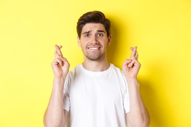 Gros plan d'un homme nerveux faisant un vœu tenant les doigts croisés et mordant la lèvre inquiet debout au-dessus de crier...