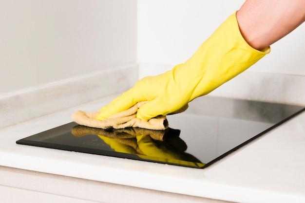Gros plan homme nettoyage cuisinière à induction