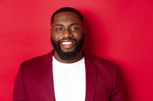 Gros plan d'un homme noir beau et élégant portant un blazer de fête, souriant heureux à la caméra