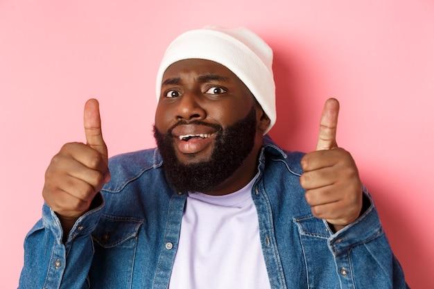 Gros plan d'un homme noir maladroit en bonnet montrant le pouce vers le haut mais se sentant grincer des dents, debout incertain et inquiet sur fond rose