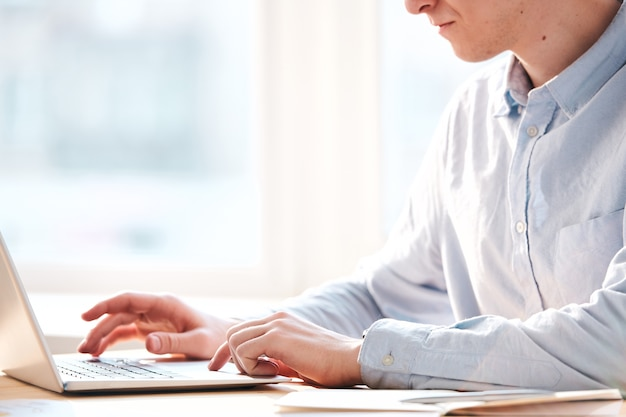 Gros plan d'un homme occupé assis à table et utilisant un ordinateur portable tout en analysant les ressources internet