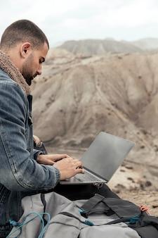 Gros plan homme avec ordinateur portable à l'extérieur
