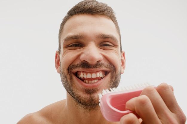Gros plan de l'homme ouvrant la bouche et montrant ses dents. jeune barbu européen souriant tenir la brosse. concept de soins dentaires. isolé sur fond blanc. prise de vue en studio
