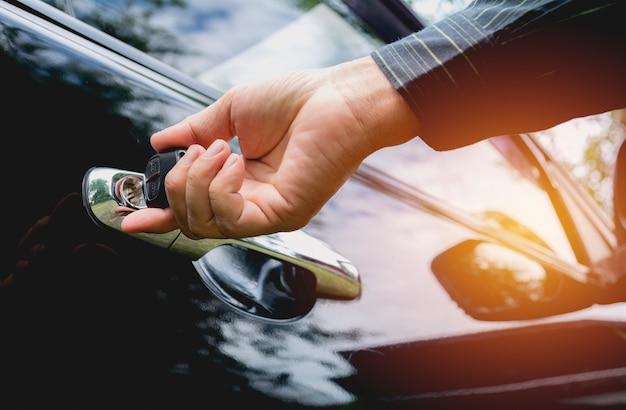 Gros plan de l'homme ouvrant une porte de voiture. main sur la poignée. homme d'affaires ouvre une voiture.