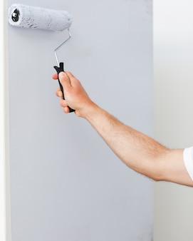 Gros plan d'un homme peignant un mur en blanc
