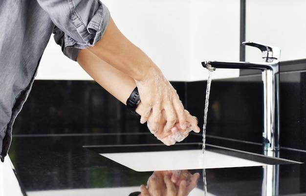 Gros plan de l'homme pendant le lavage des mains avec du savon, concept d'hygiène