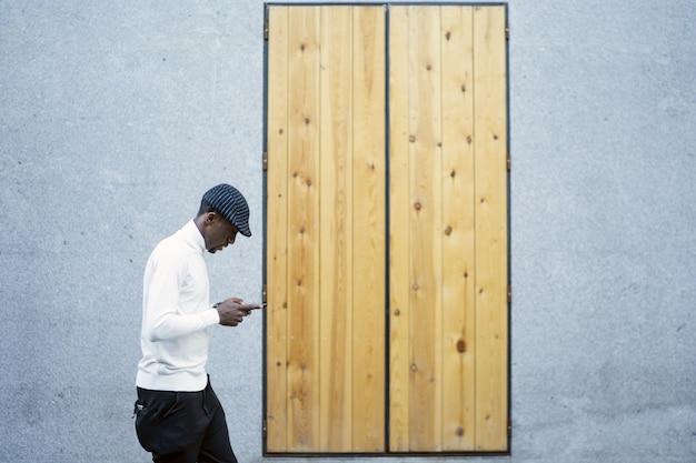Gros plan d'un homme portant un chapeau et un col roulé en regardant son téléphone