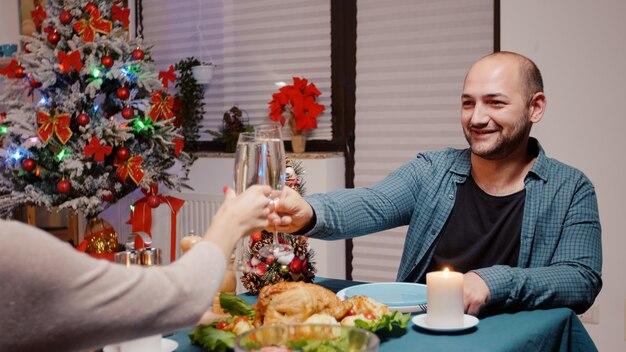 Gros plan d'un homme profitant d'un dîner de fête et de verres tintants