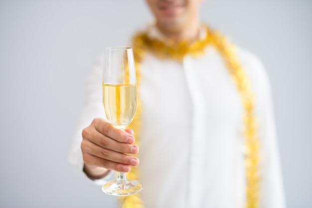 Gros plan d'un homme qui élève un verre de champagne