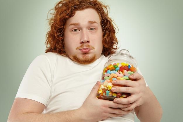 Gros plan d'un homme de race blanche grassouillet triste avec des cheveux bouclés au gingembre tenant un pot de marmelades