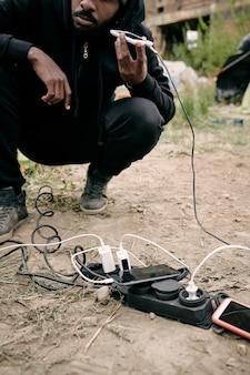 Gros plan sur un homme réfugié noir accroupi à la prise de courant et écoutant un message audio au téléphone tout en le chargeant à l'extérieur