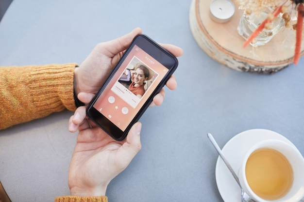 Gros plan d'un homme regardant la photo de la belle fille tout en utilisant l'application de rencontres en ligne sur son téléphone mobile