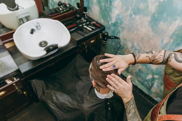 Gros plan d'un homme se faisant couper les cheveux à la mode au salon de coiffure. le coiffeur masculin en tatouages au service du client.