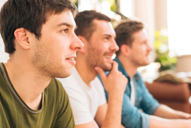 Gros plan, homme, séance, amis, regarder, télévision