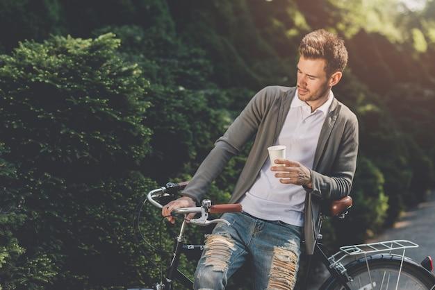 Gros plan, homme, séance vélo, à, jetable, café, tasse