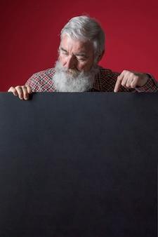 Gros plan d'un homme senior avec une barbe grise, pointant son doigt sur une pancarte noire vierge