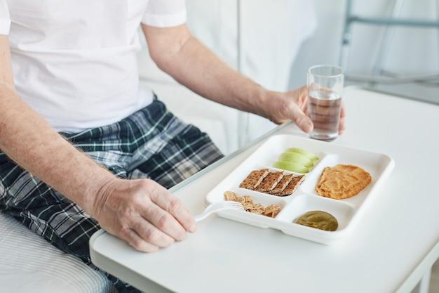 Gros plan d'un homme senior méconnaissable mangeant de la nourriture sur un plateau dans l'espace de copie de la chambre d'hôpital