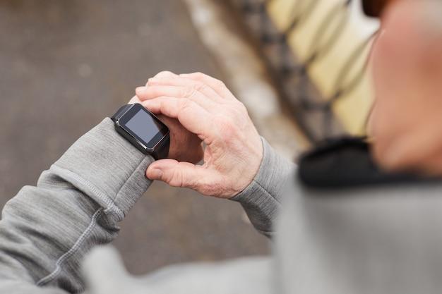 Gros plan d'un homme senior moderne vérifiant la montre intelligente tout en courant à l'extérieur en hiver, espace de copie