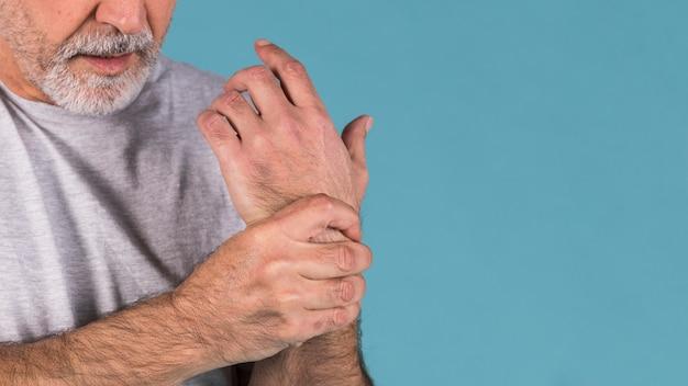 Gros plan d'un homme senior tenant son poignet douloureux