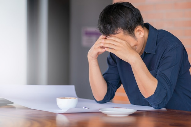 Gros plan d'un homme sérieux occasionnel assis la tête dans les mains au bureau