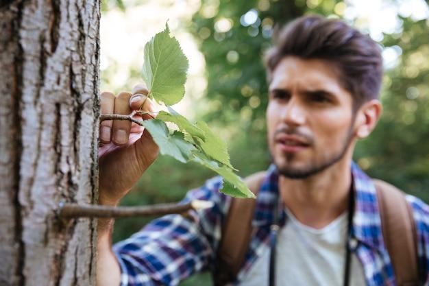 Gros plan homme sérieux près de l'arbre