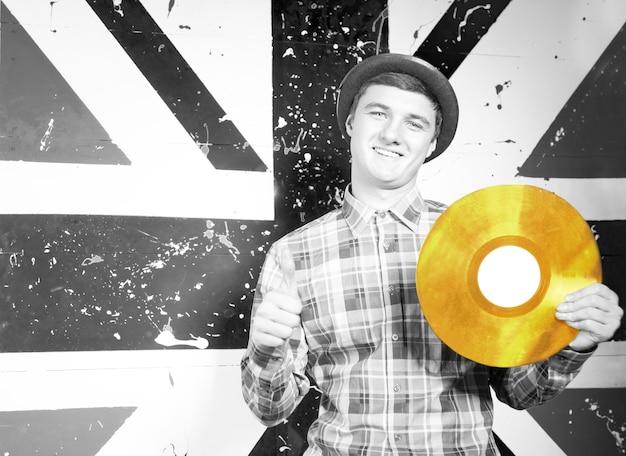 Gros plan sur un homme souriant dans un style monochrome tenant une plaque de disque vinyle doré devant l'impression du drapeau britannique.