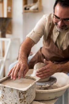 Gros plan homme souriant faisant de la poterie