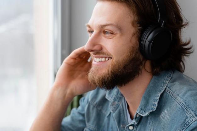 Gros plan homme souriant portant des écouteurs