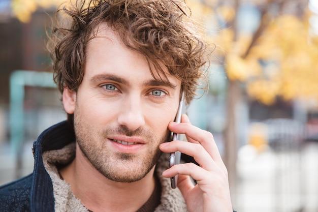 Gros plan d'un homme souriant séduisant parlant au téléphone mobile