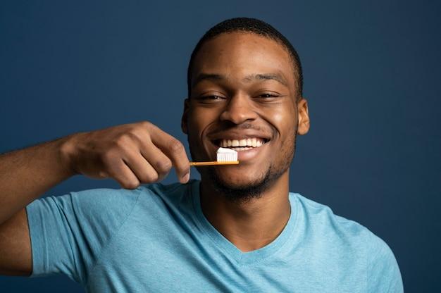 Gros plan homme souriant tenant une brosse à dents