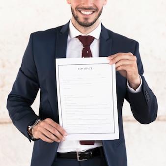 Gros plan homme souriant tenant un contrat
