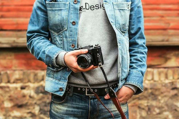Gros plan sur un homme tenant un appareil photo vintage en plein air