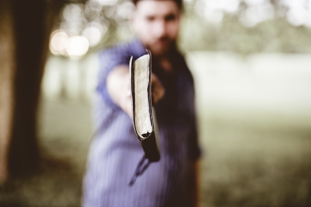 Gros plan d'un homme tenant la bible vers la caméra