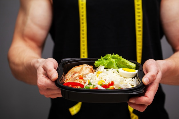 Gros plan d'un homme tenant une boîte pleine d'aliments riches en protéines pour la nutrition sportive