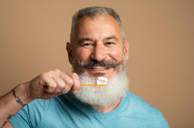 Gros plan homme tenant une brosse à dents